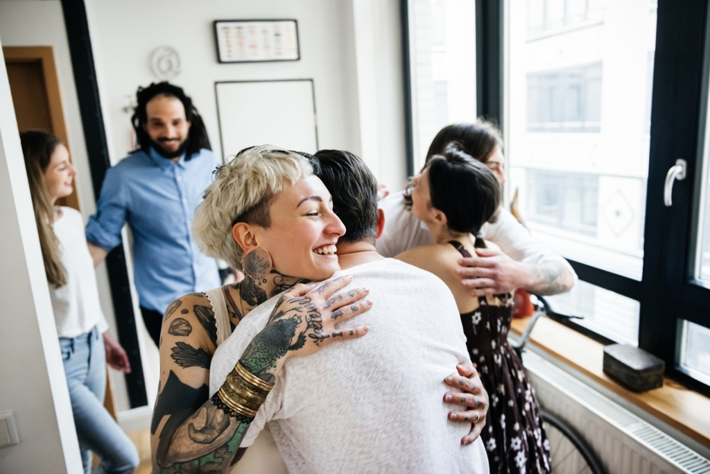 Women with short blond hair and tattoos hugging house guests