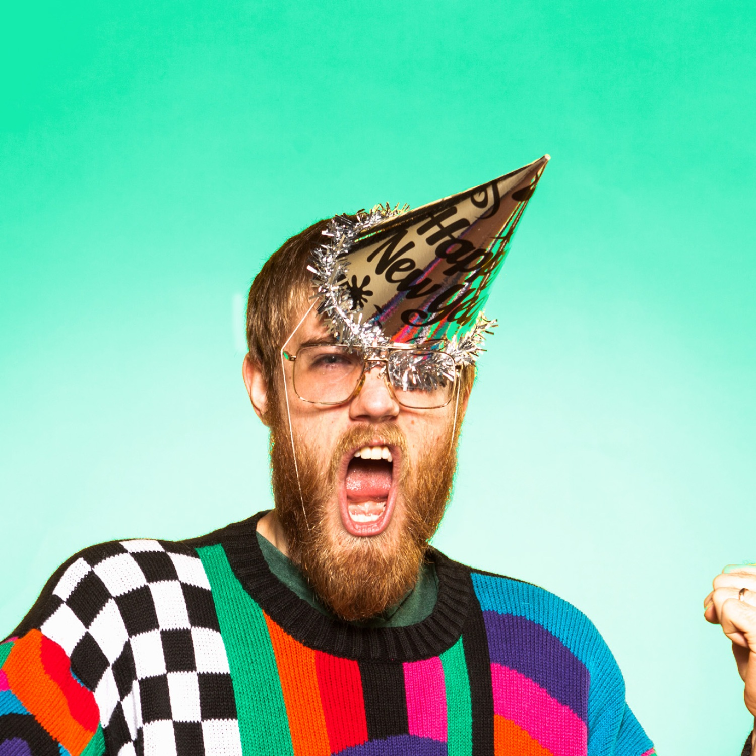 Bearded man in ugly sweater with New Year's party hat
