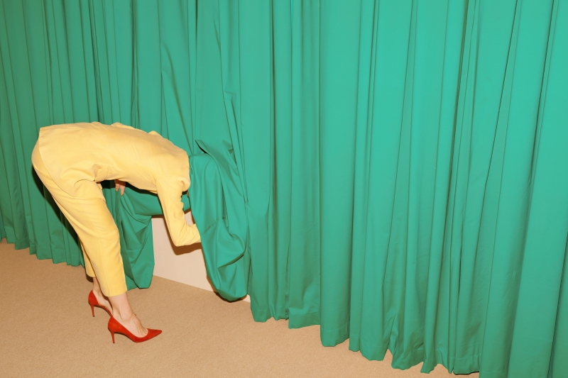 Woman in yellow suit poking around underneath teal curtains