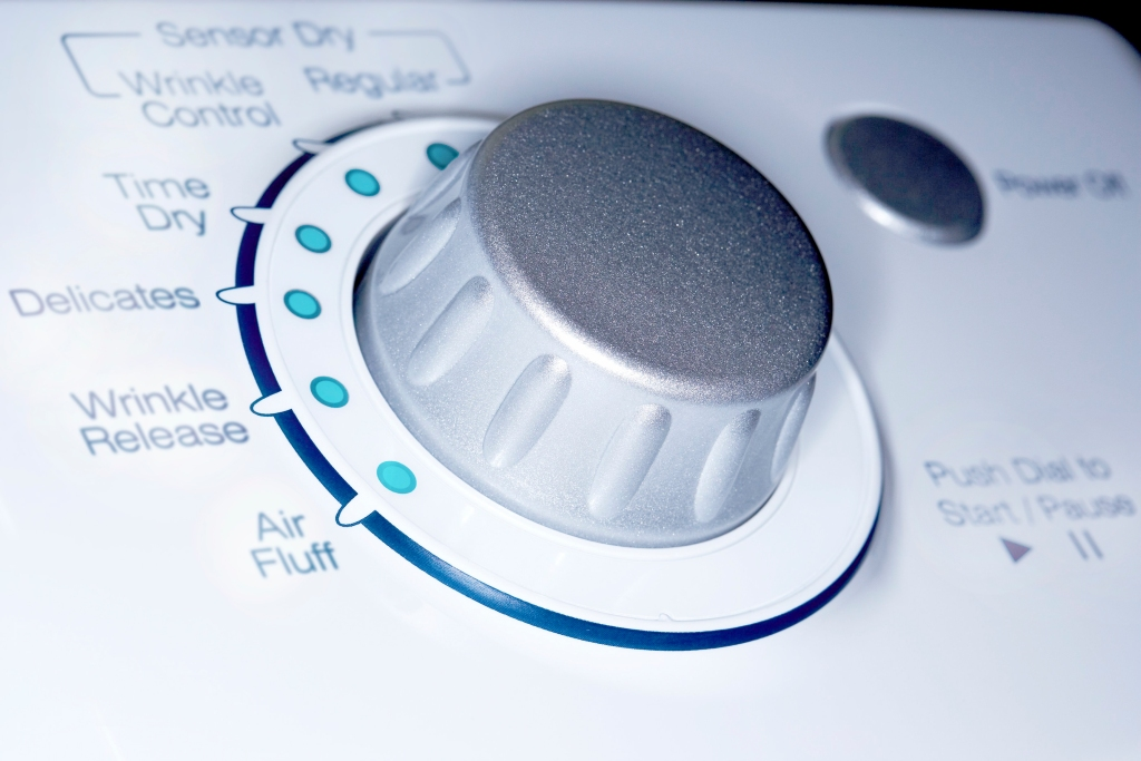 Close up of silver dial on white dryer | Safely clean dryer