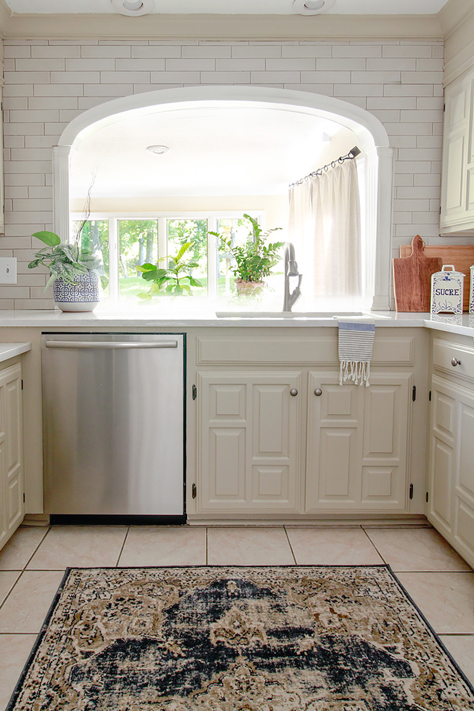 White kitchen with white tile backsplash along archway