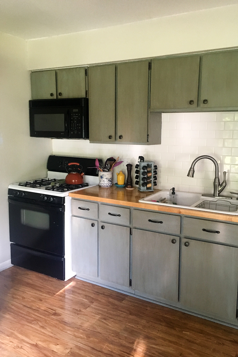 Olive and gray kitchen cabinets awaiting door replacement