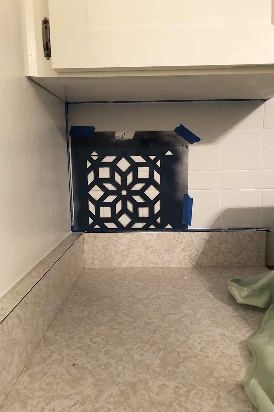 White tile with stencil taped to it for DIY tile upgrade