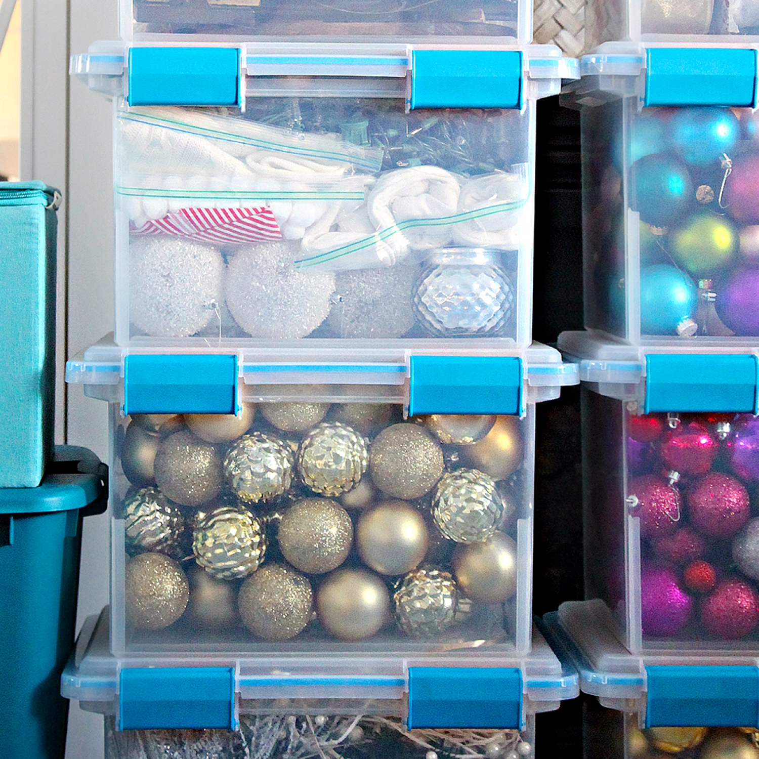 Holiday decorations stacked in large, clear plastic tubs