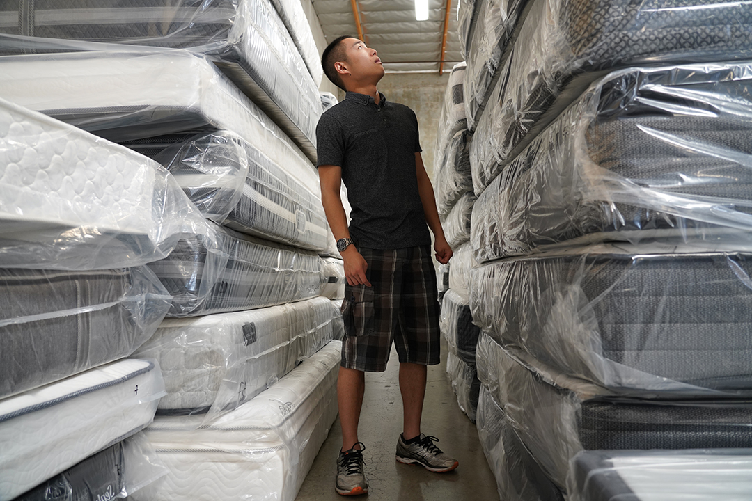 Man in warehouse looking up at tower of mattresses