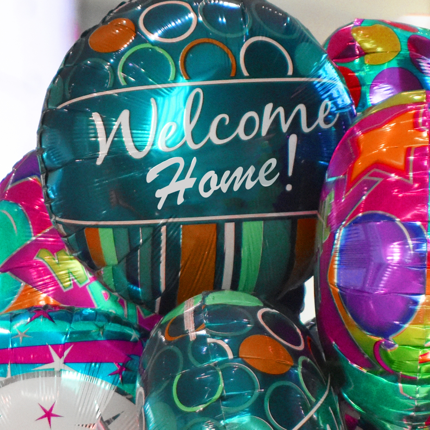 "Assortment of foil balloons that say, ""Welcome home!"""