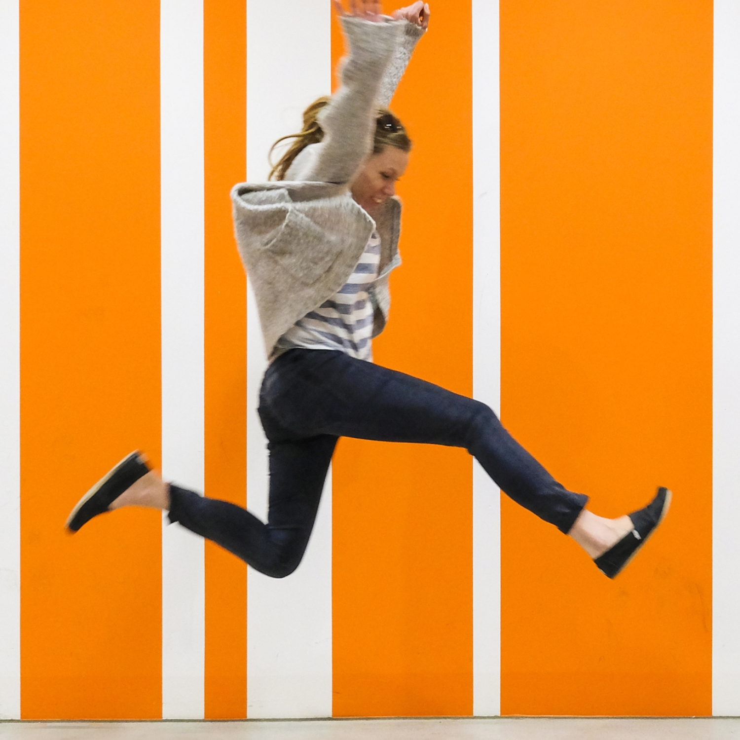 Woman jumping for joy against orange striped background