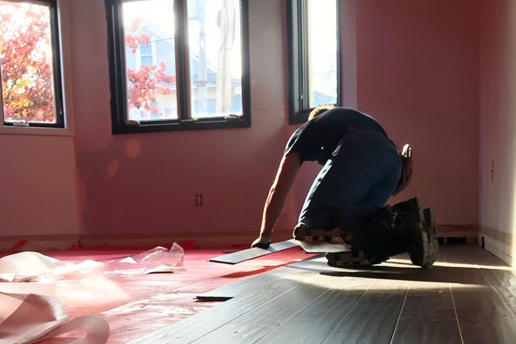 Man on hands and knees laying boards for wood floor