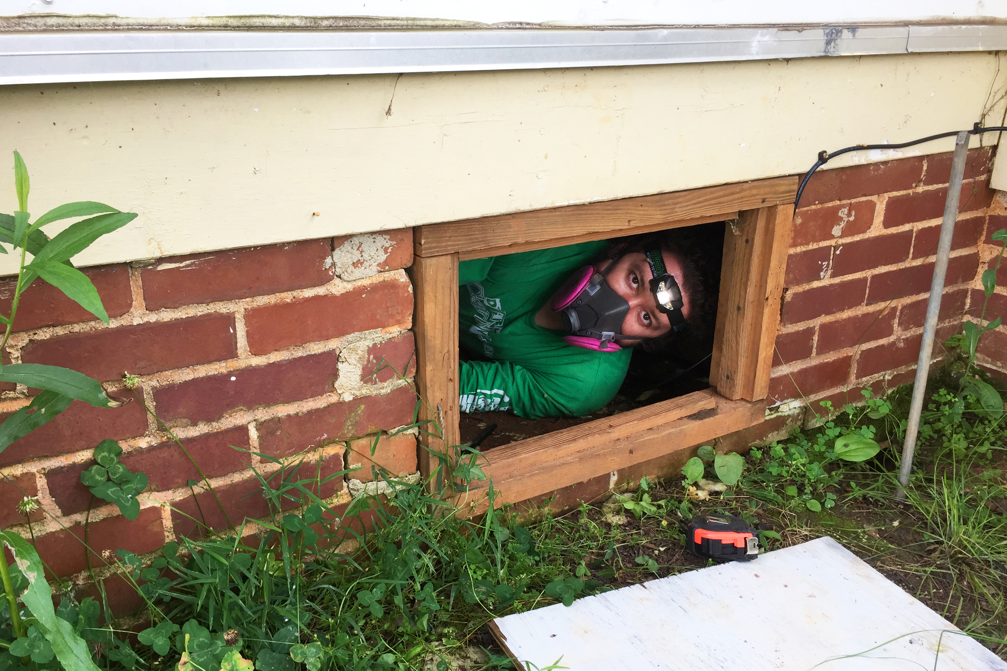 Man with respirator mask on peering out from basement window