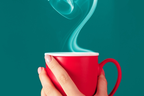 Hand holding red mug with heart-shaped smoke from beverage
