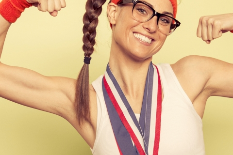 Woman with glassesin workout gear with medals flexing biceps