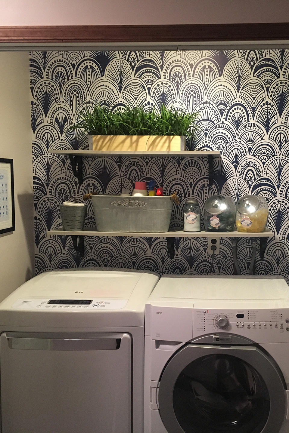 Neatly organized laundry closet with shelves and wallpaper