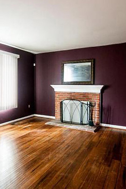 Empty room with purple walls, wood floor and brick fireplace