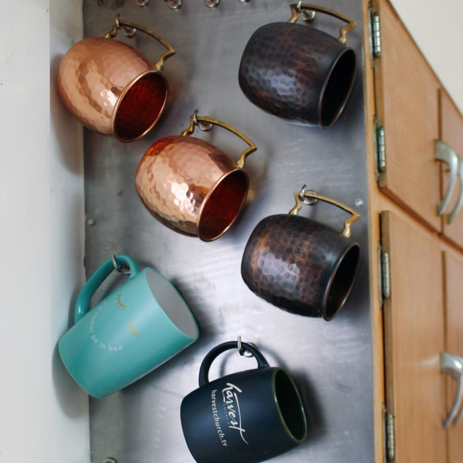 Assorted copper and ceramic mugs hanging on side of cabinet