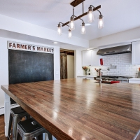 Large wooden kitchen island in front of chalk board