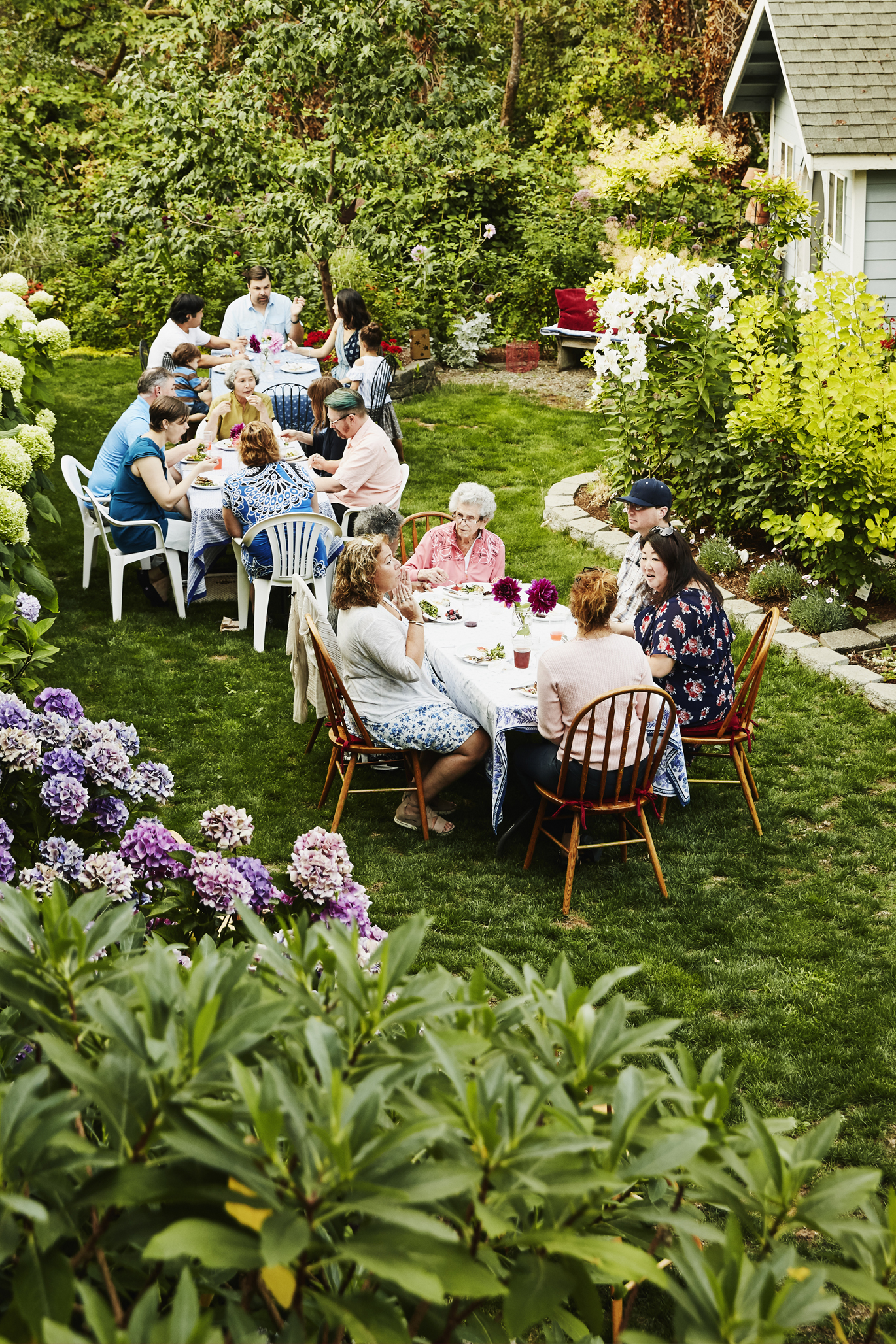 Families gathered at two tables enjoying time in backyard
