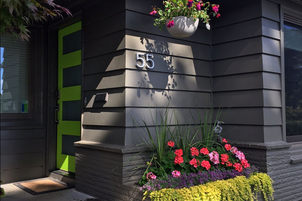 Dark gray house with lime green door and flower beds
