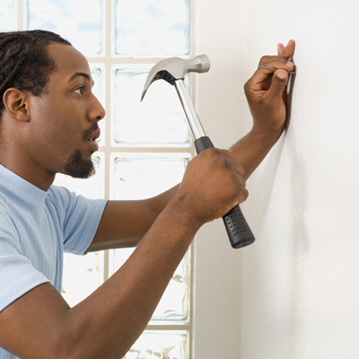 DIYer hammering a nail in the wall of his home