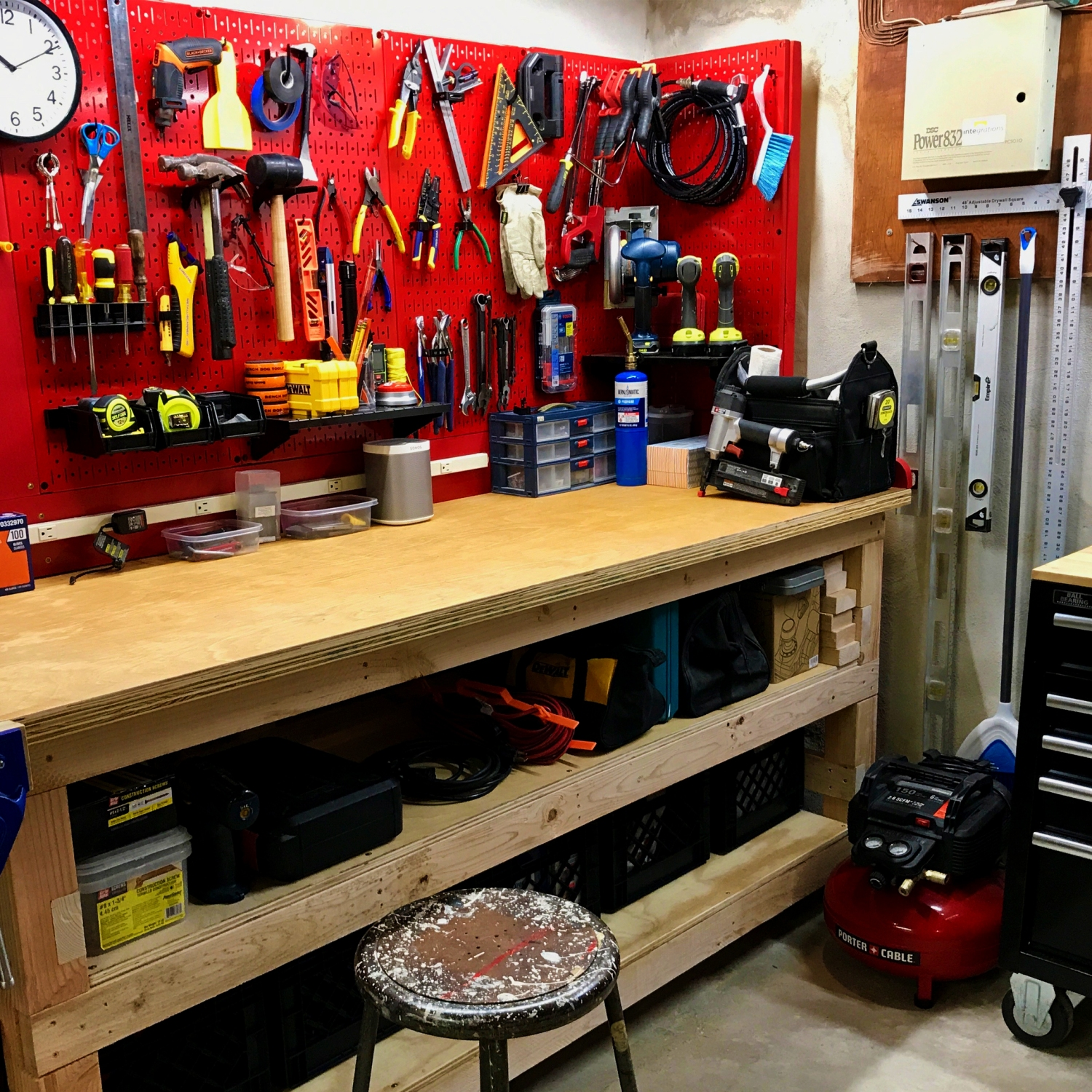 Wooden work bench with red peg board covered in tools