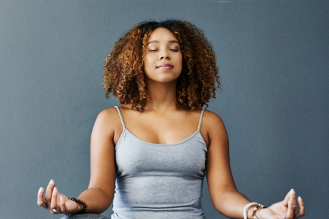 Woman in lotus pose meditating with eyes closed on yoga mat