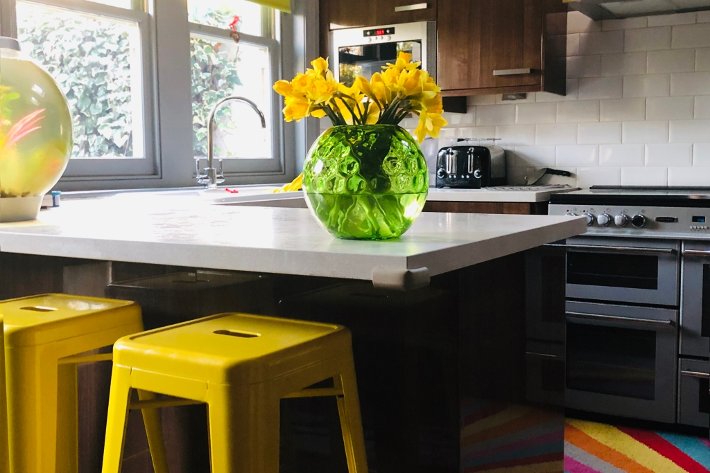 Sunny kitchen with neutral countertop and bright yellow tolix stools