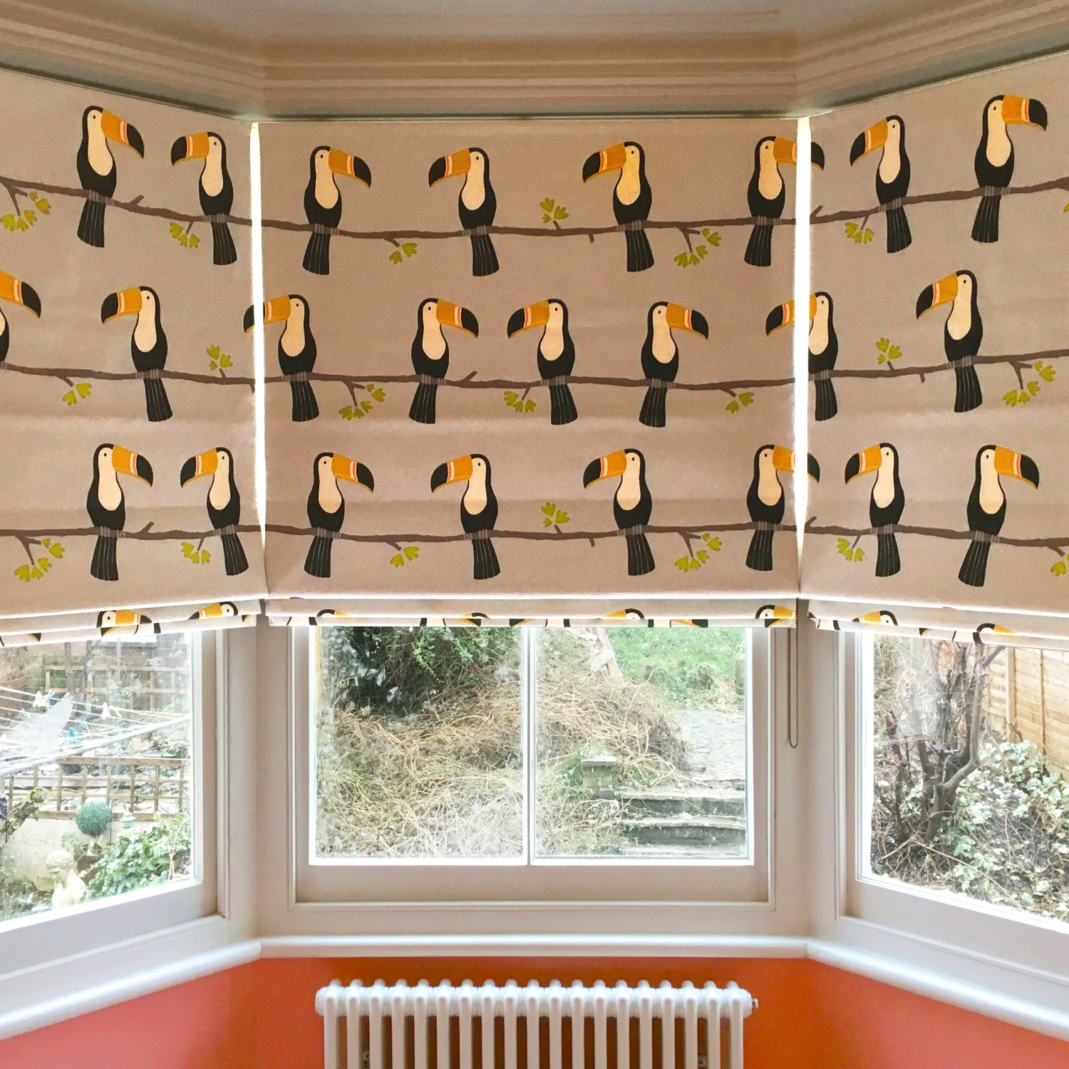 Roman shades in bay window with a toucan print