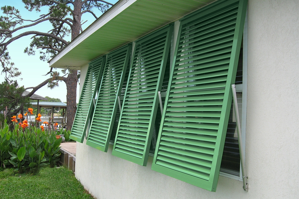 Green hurricane shutters installed at a house