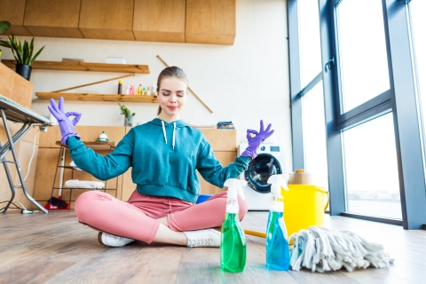 smiling young woman sitting on floor and meditating while cleaning house