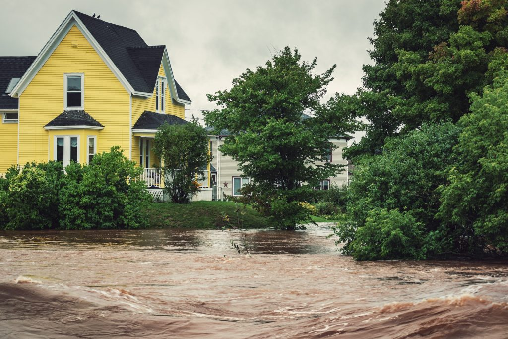 yellow house near a raging river overflowing its banks